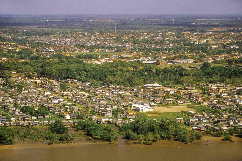 Foto aérea do Amapá com cidade na beira de rio.