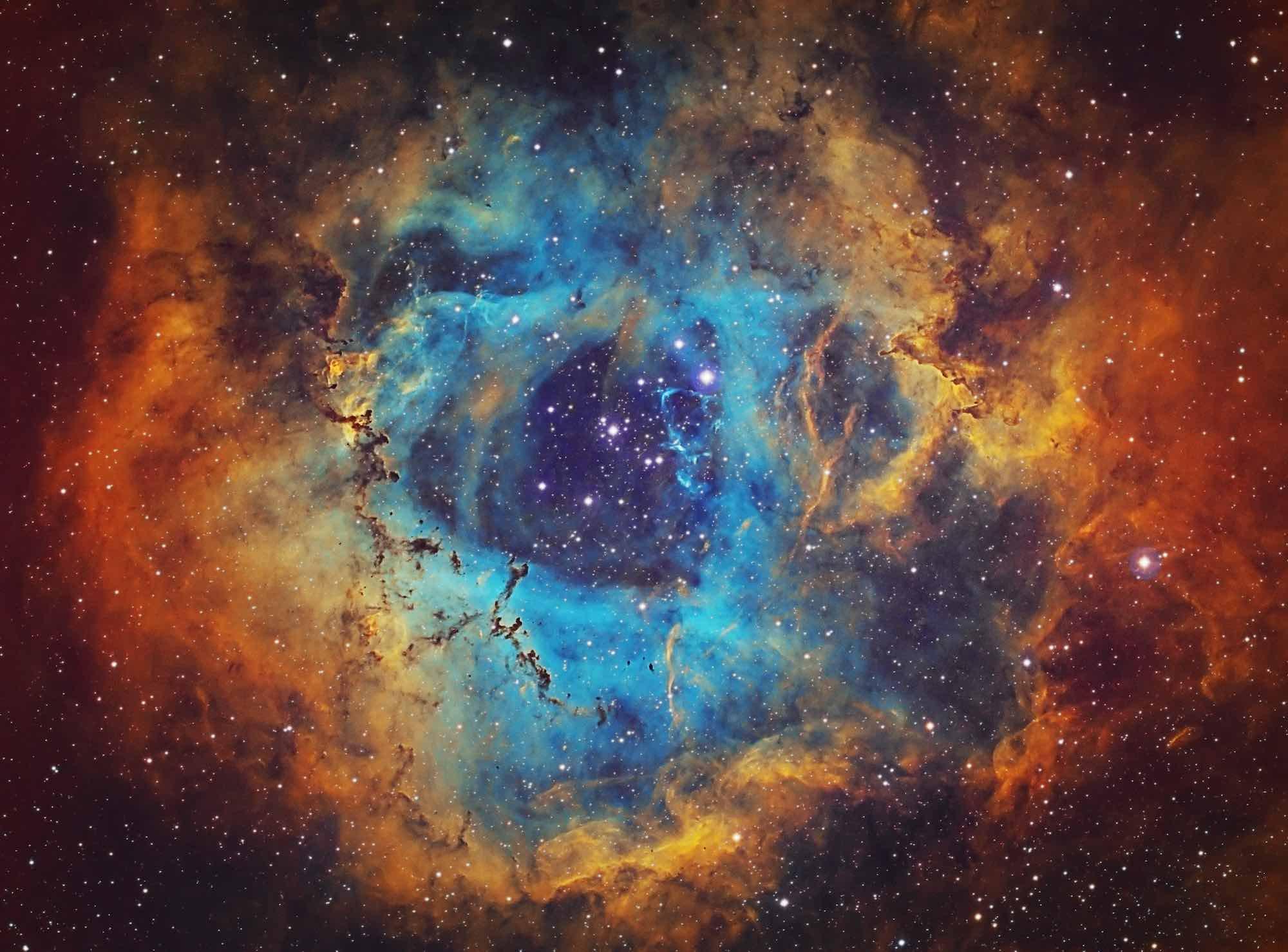 Foto da Nebulosa Roseta (NGC 2237, Caldwell 49) que é a grande nuvem de hidrogênio, enxofre e gás oxigênio na constelação de Monoceros. O aglomerado de estrelas aberto NGC 2244 (Caldwell 50) consiste em estrelas sendo formadas a partir da nebulosa. A nebulosa está a 5.200 anos-luz de distância da Terra. Imagem amadora, tempo total de exposição: 15h45m, imagem da paleta HST.