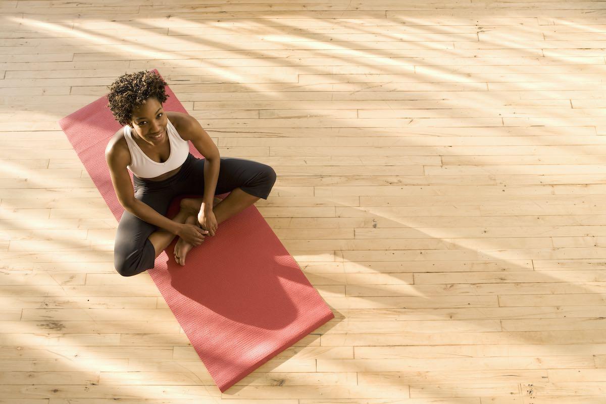 Mulher sentada sobre esteira de exercícios em piso de madeira, olhando para o alto.