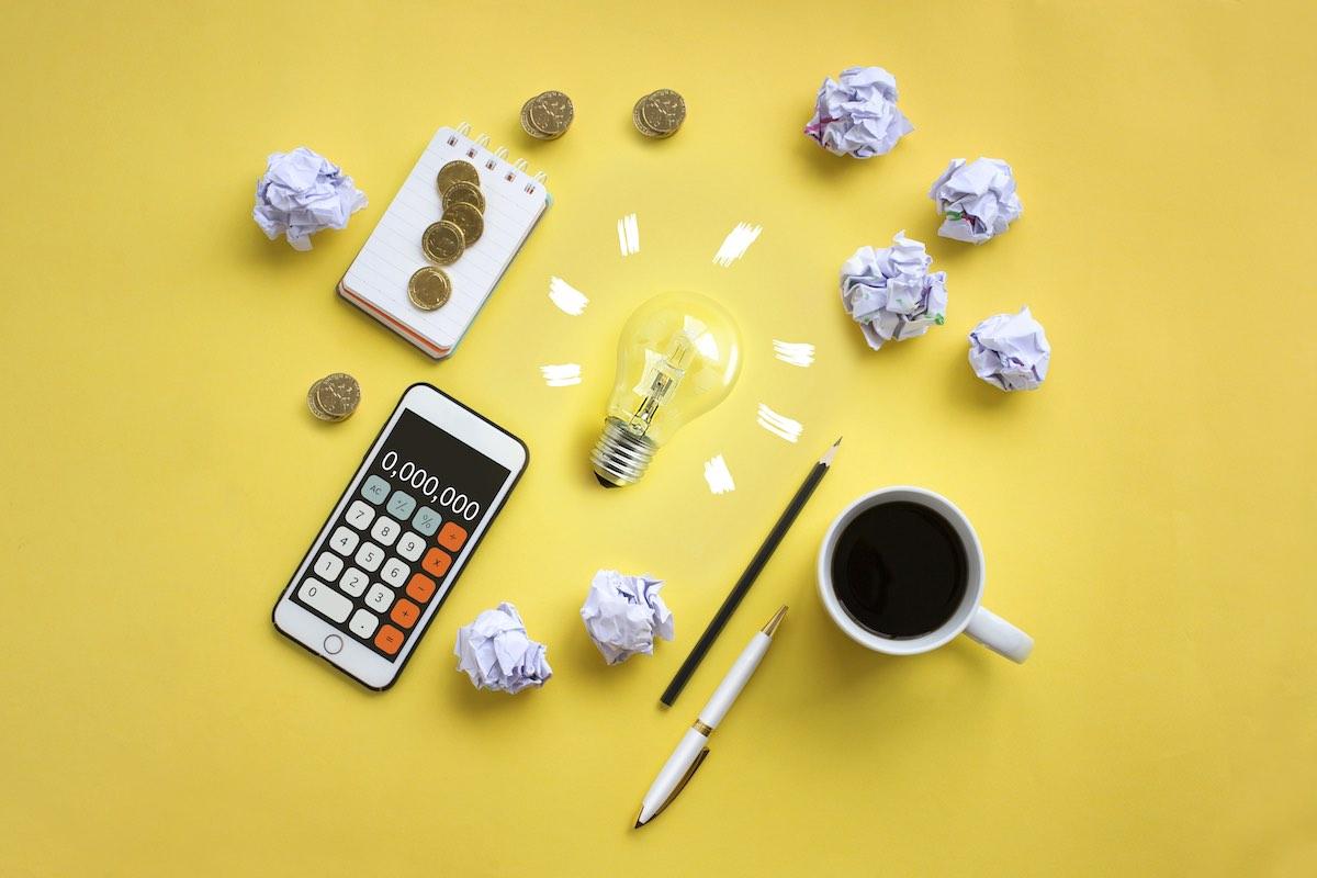 Imagem de calculadora, moedas, caneca com bebida e bloco de anotações visto do alto, sobre fundo amarelo.