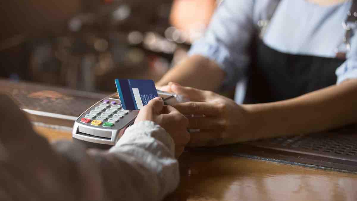 Foto de pessoa segurando cartão de crédito próximo a máquina de cartões.