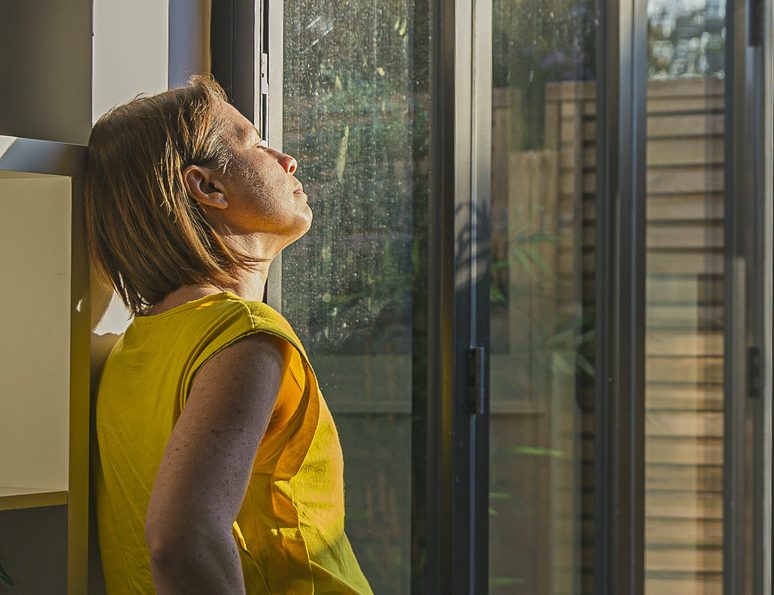 File image of a woman leaning on a bookshelf by a window with her face bathed in sunlight.