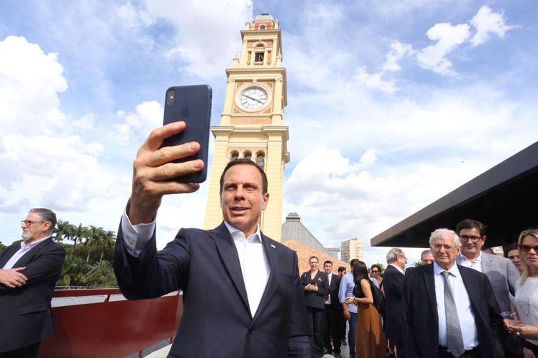 A imagem mostra João Dória, de costas para um grupo de pessoas, tirando uma selfie com o Museu da Lingua Portuguesa ao fundo durante sua reinauguração.
