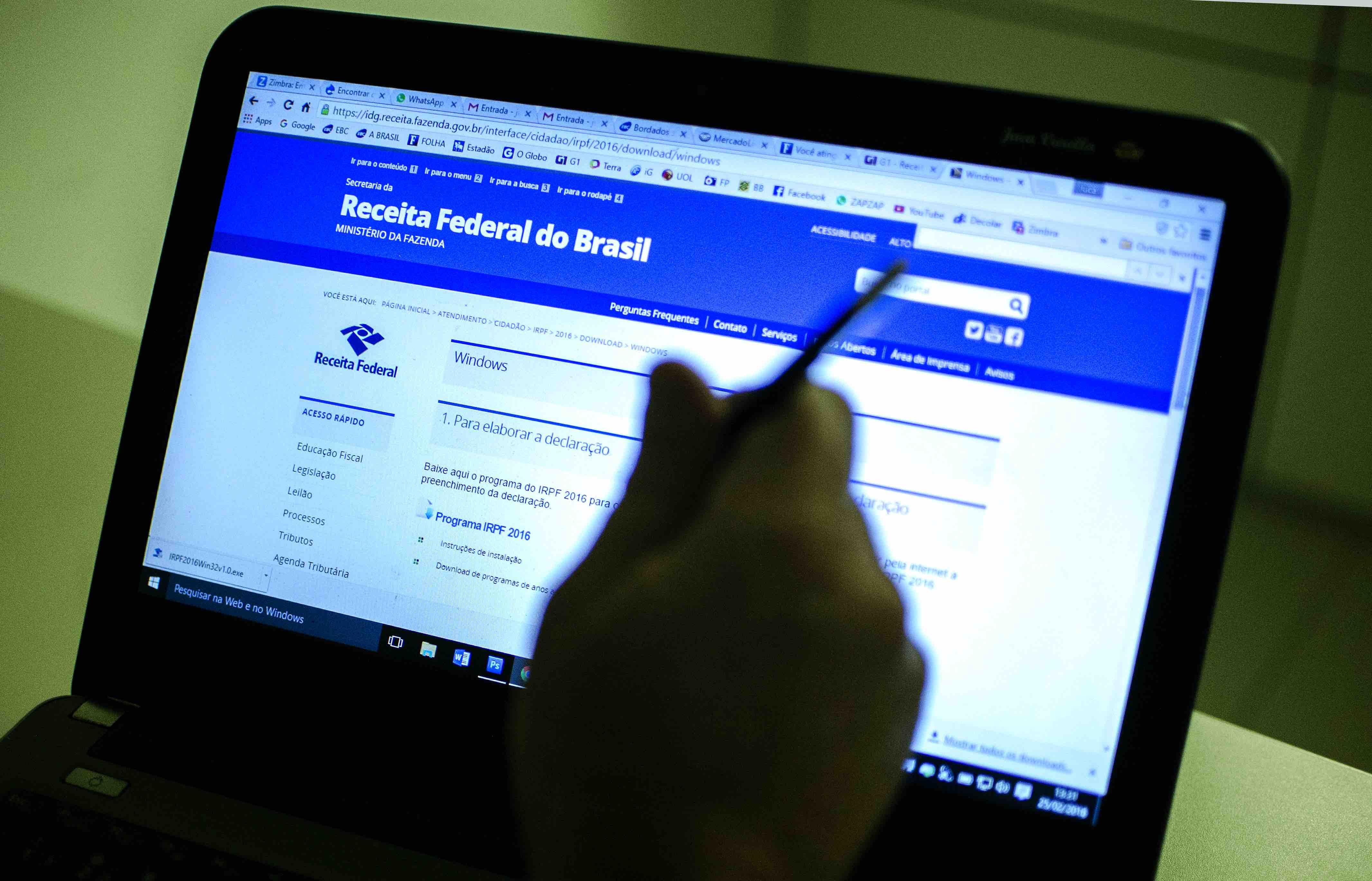 Imagem de notebook ligado sobre uma superfície com a tela exibindo o site da Receita Federal do Brasil e uma mão desfocada em frente ao notebook vista segurando uma caneta.