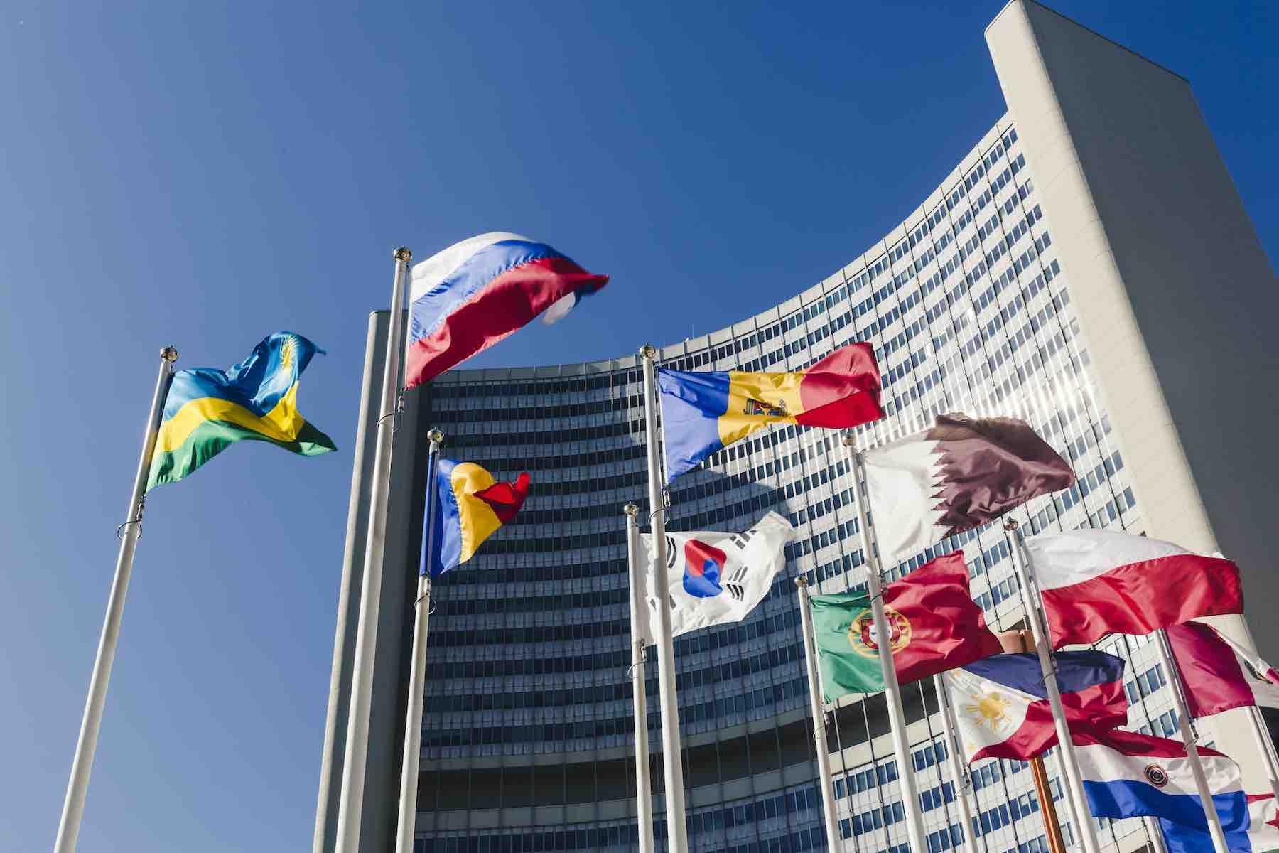 Bandeiras de países hasteadas em frente a um edifício.