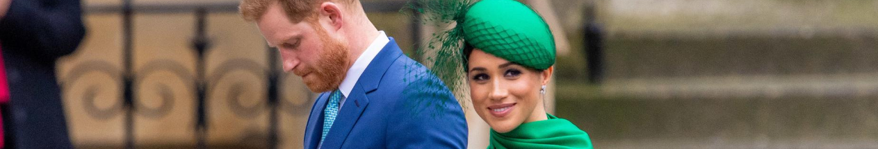 Meghan Markle, Duchess of Sussex, smiles as she enters Wesminster Abbey with Prince Harry on her last royal engagement. She is wearing an emerald green hat and cape.