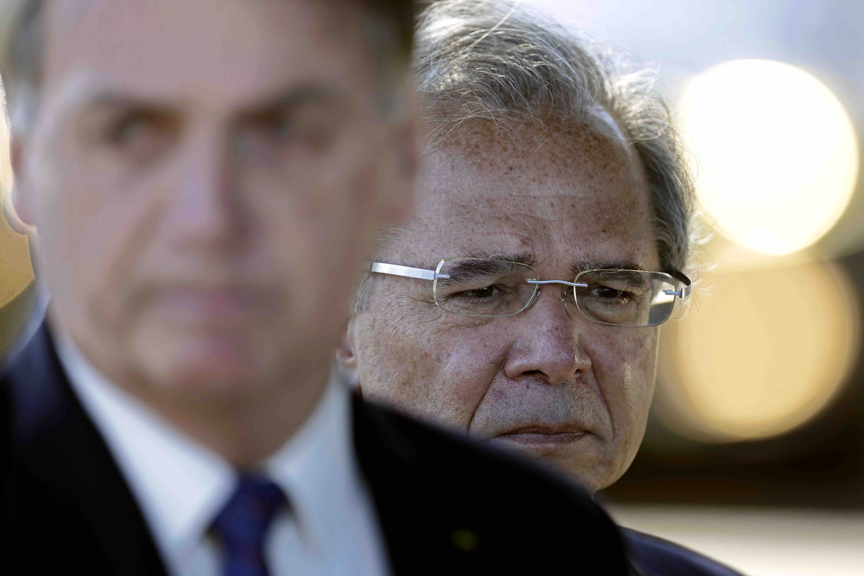 Ministro da Economia do governo Bolsonaro, Paulo Guedes é visto atrás do presidente.