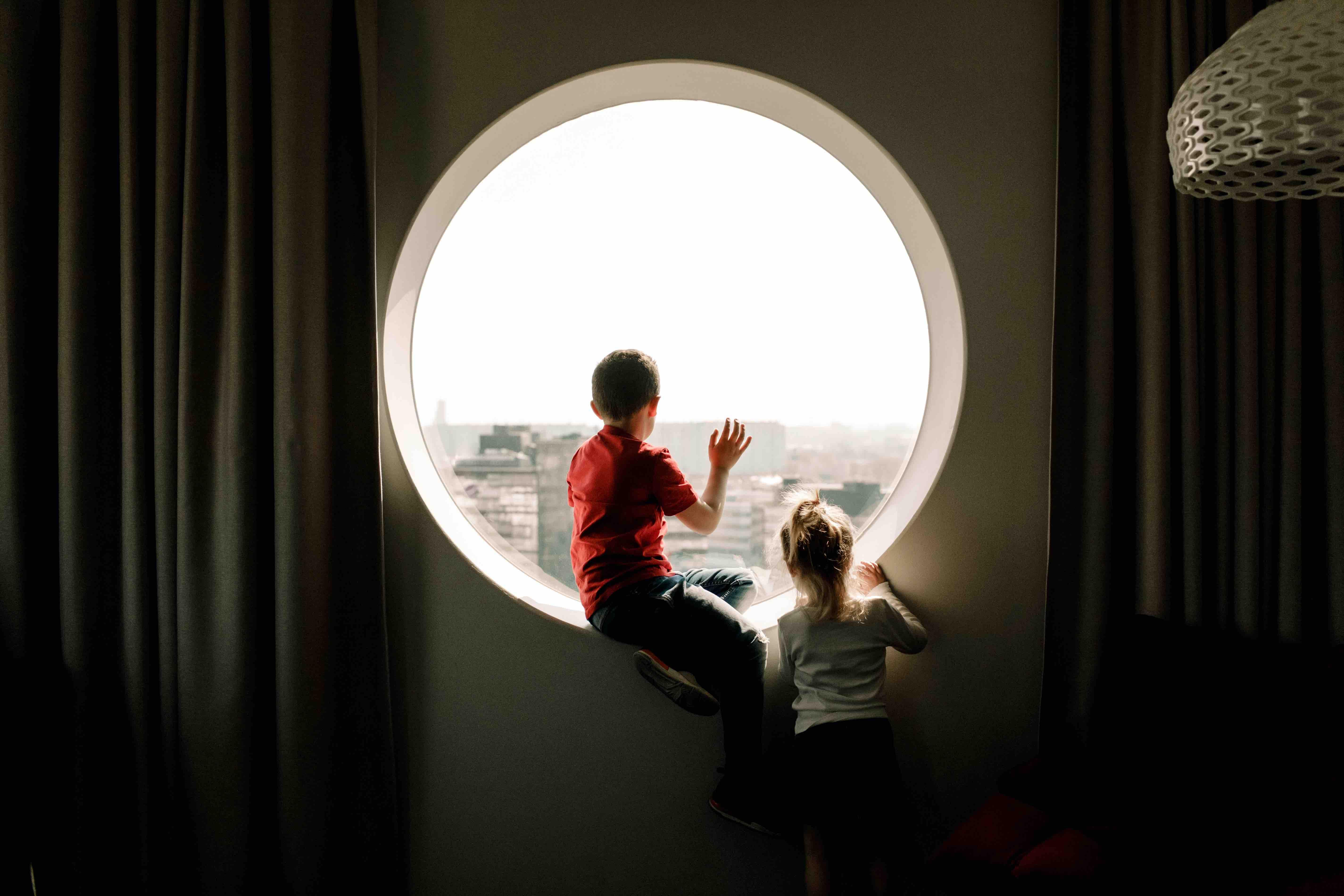 Duas crianças olhando para o lado de fora de um ambiente, através de uma janela circular