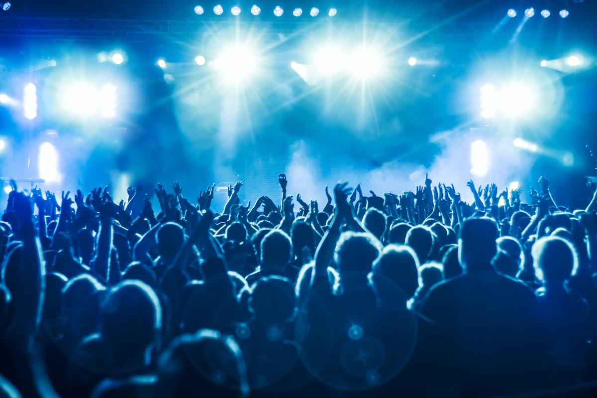 Imagem de pessoas com mãos levantadas durante um show