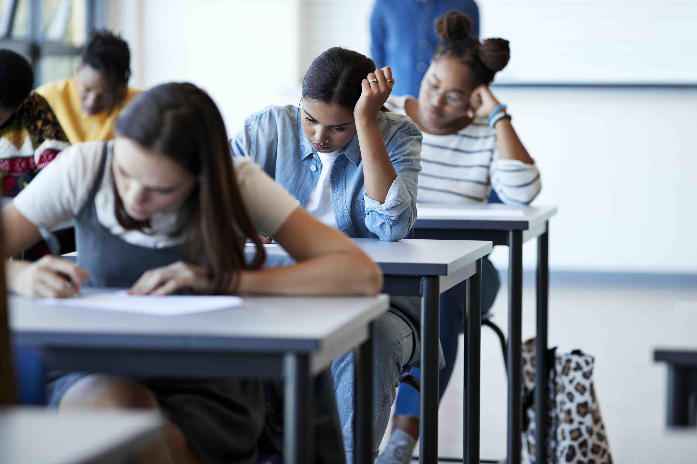 Mulheres estudantes fazem prova em uma sala de aula. Elas estão enfileiradas, uma atrás da outra escrevendo no papel que está na mesa a frente.