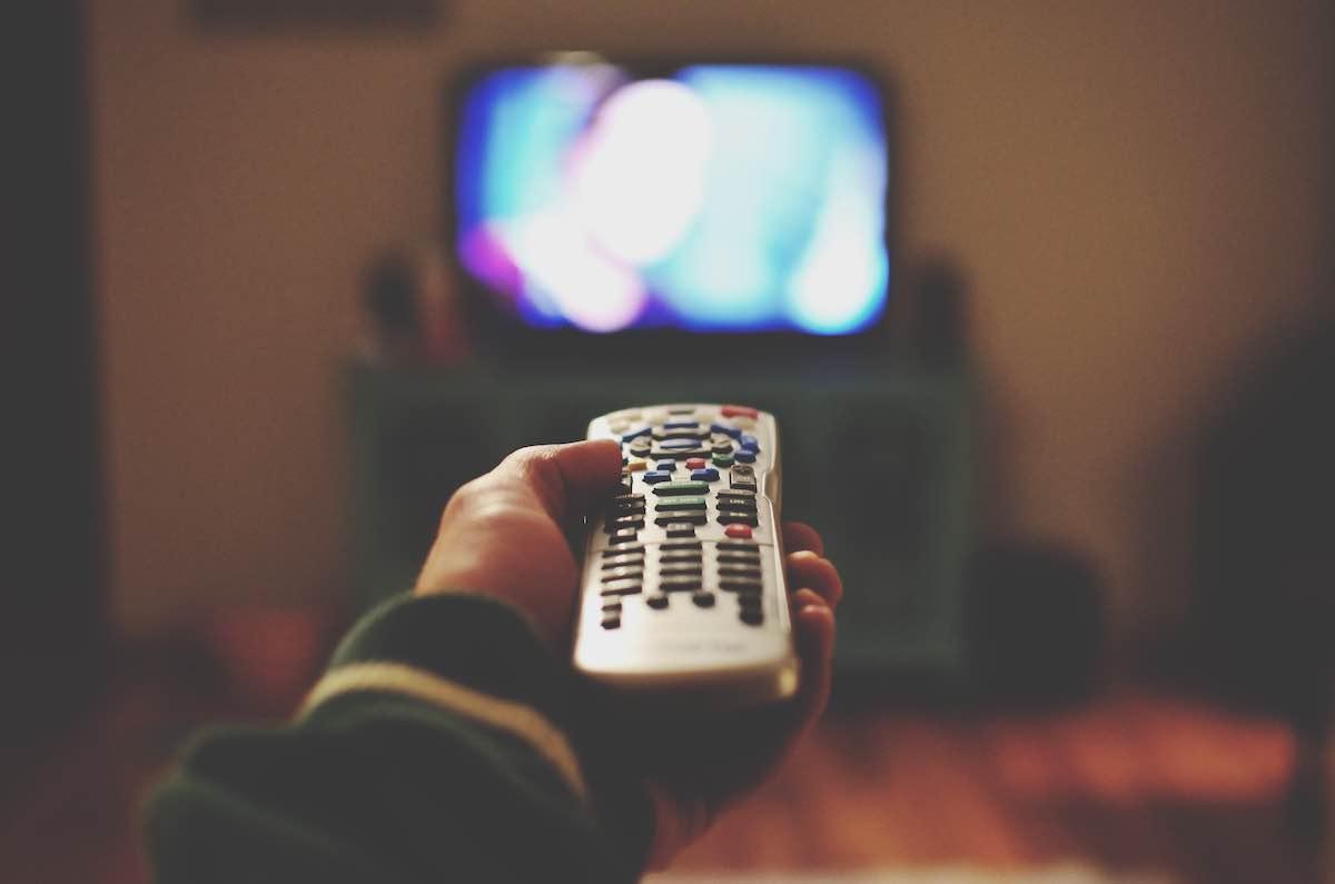 Pessoa segurando controle remoto, apontando para uma televisão ligada.