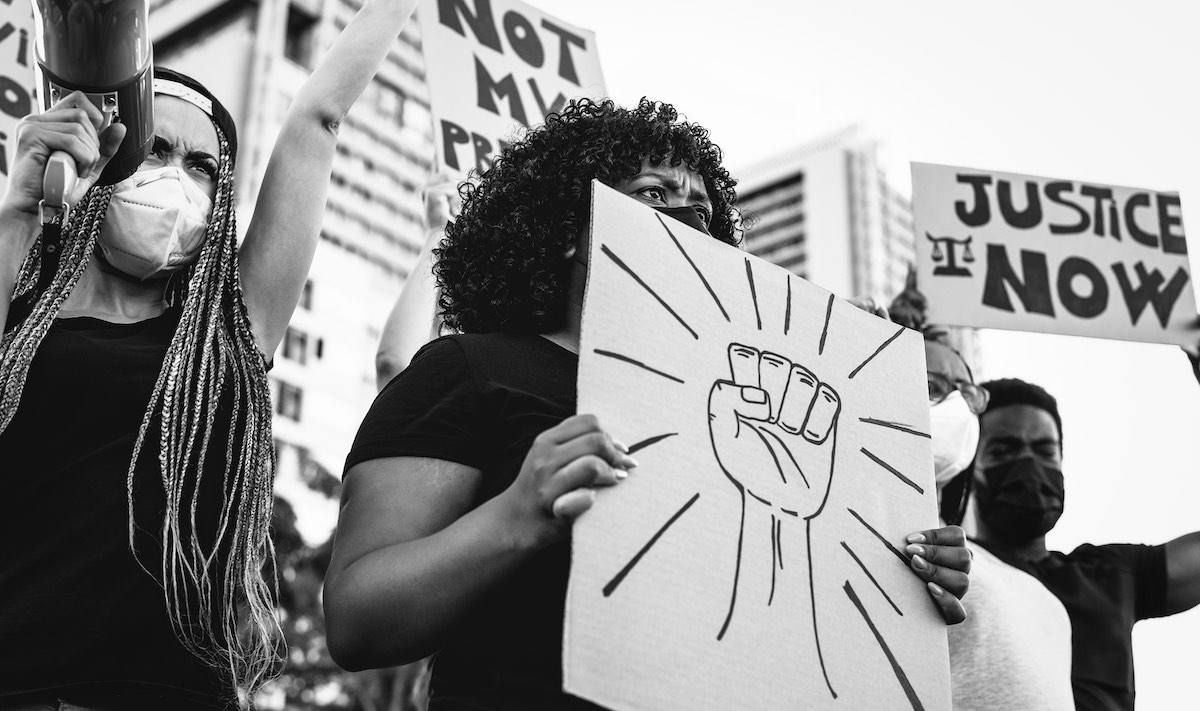Mulheres negras protestando usando cartazes com palavras de ordem contra o racismo.