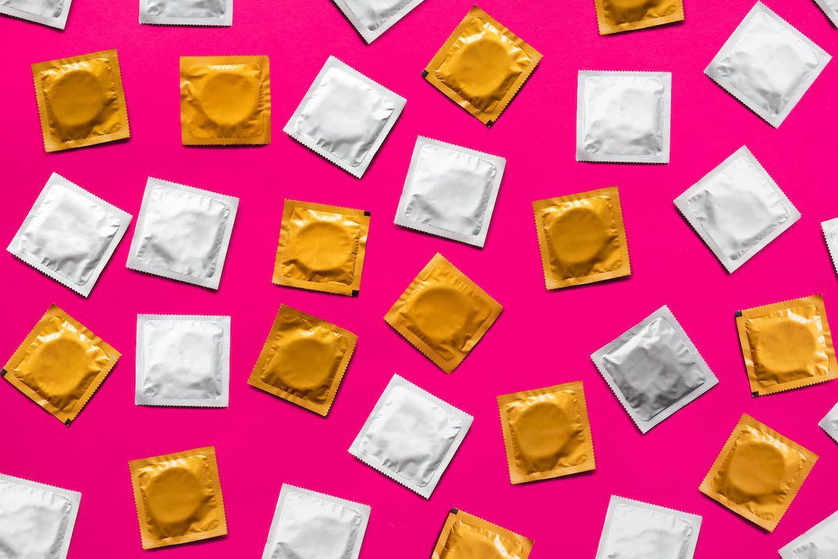 Foto de camisinhas na embalagem original, sobre fundo pink
