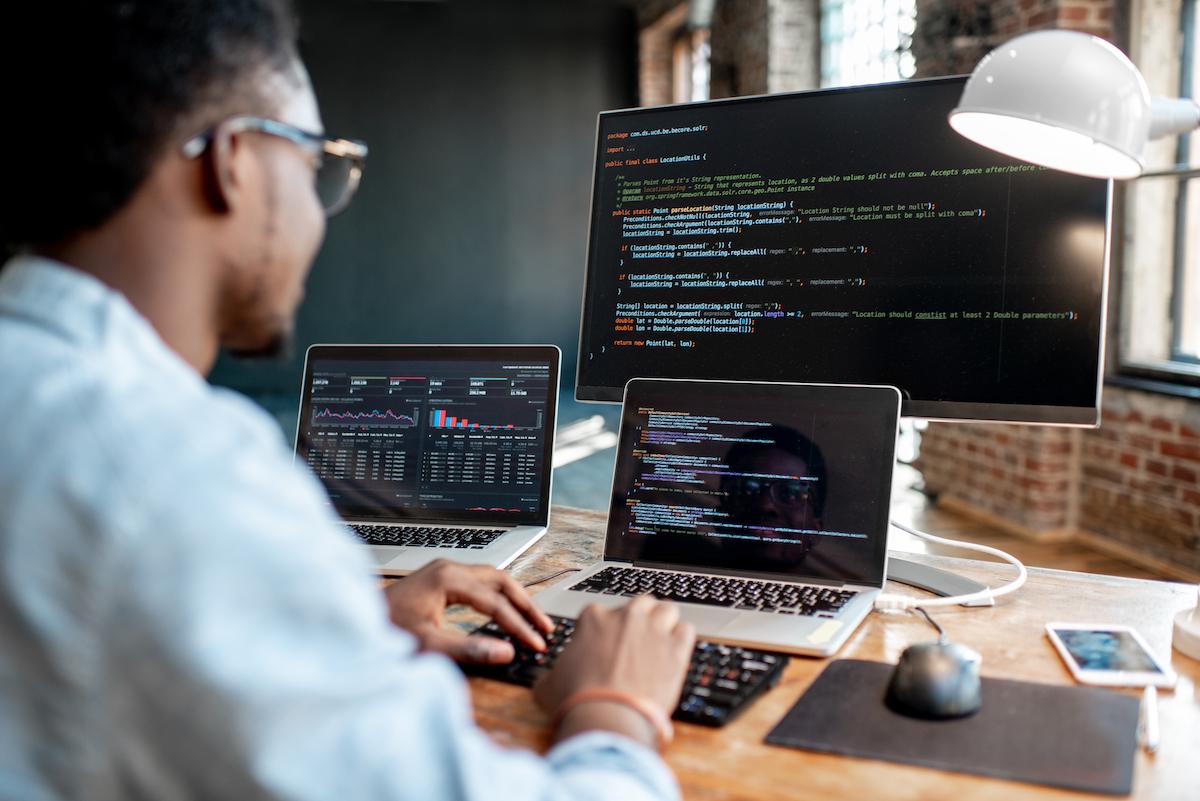Foto de homem observando código de programação em tela de notebook e monitor.