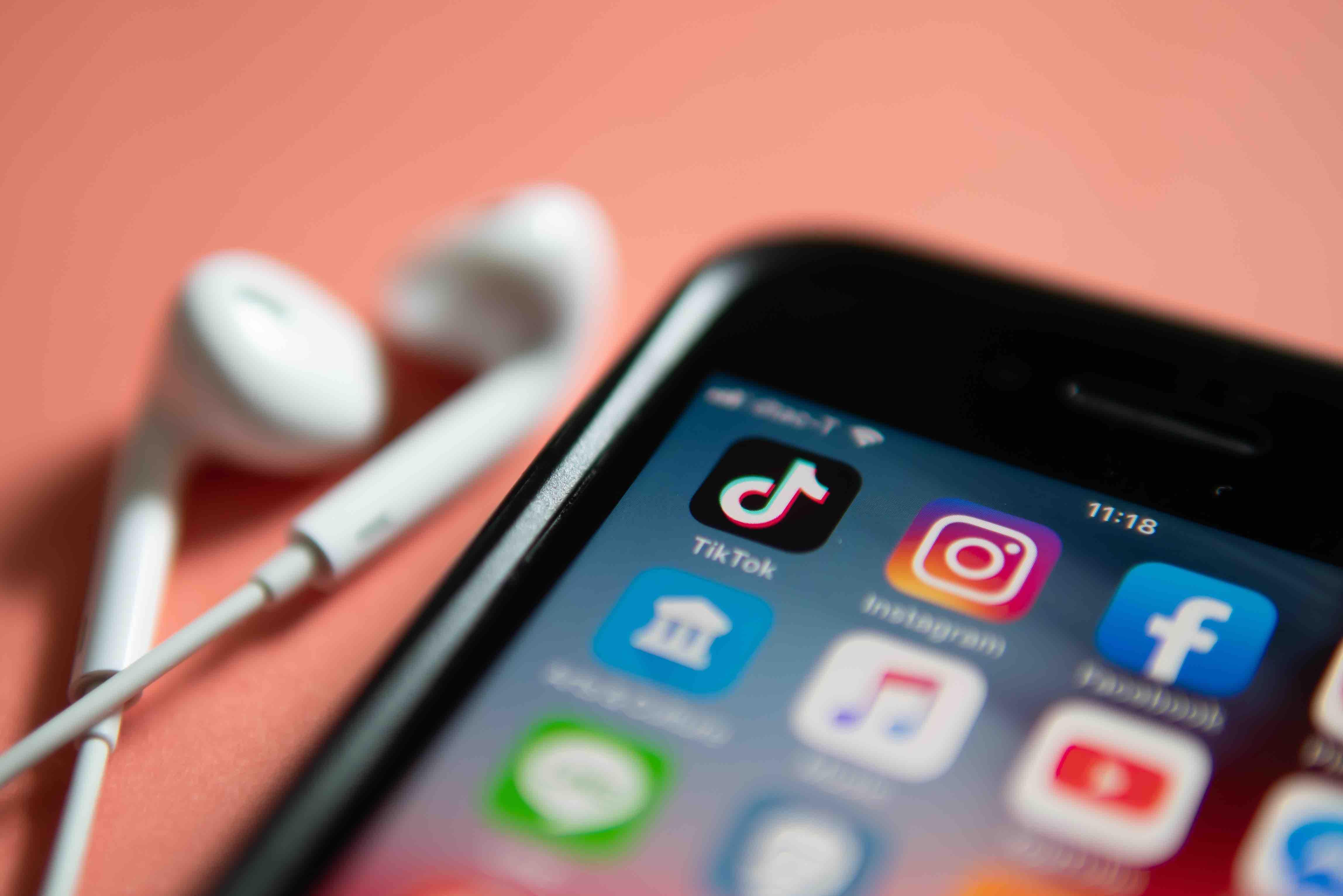 foto de smartphone ao lado de fones de ouvido com ícones de redes sociais