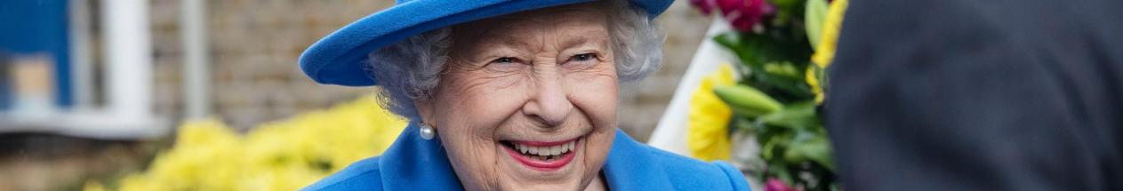 Queen Elizabeth II smiles broadly, wearing a bright blue hat and pearl earrings.
